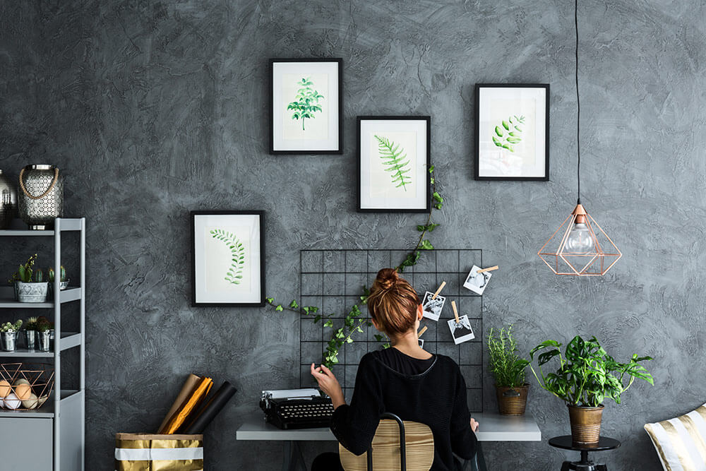 Woman sitting at desk in loft style apartment with grey walls and prints of plants on the wall