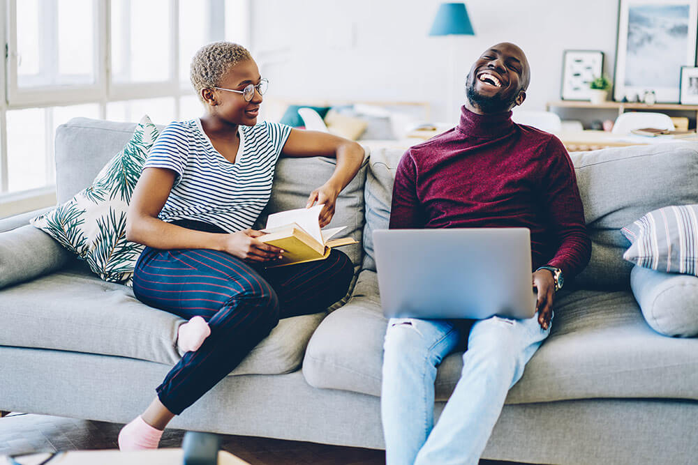 Couple sitting and laughing on couch, woman with book and man on laptop