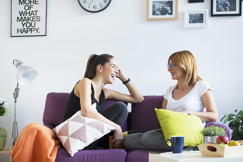 Two young women sitting on couch talking and laughing in loft style apartment