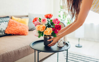 Woman putting small vase with colorful flowers on coffee table in living room