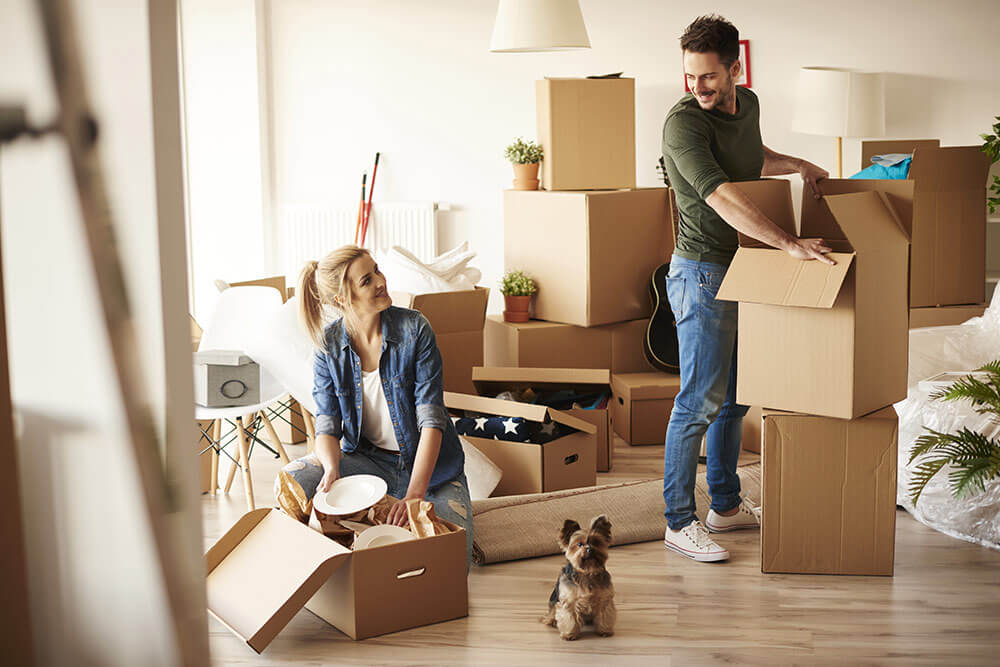 Young couple unpacking in new apartment, smiling and happy