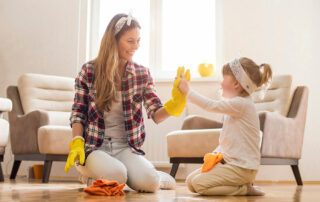 Woman and daughter high five while cleaning living room in downtown loft apartment