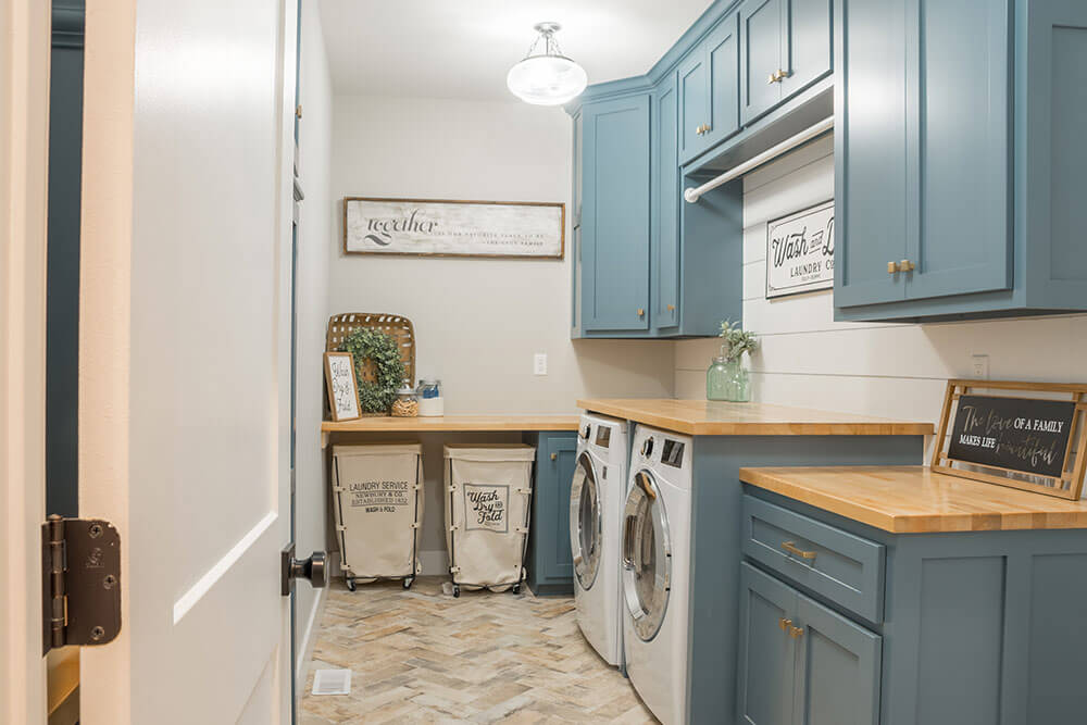 Cute laundry space, well organized with cabinets