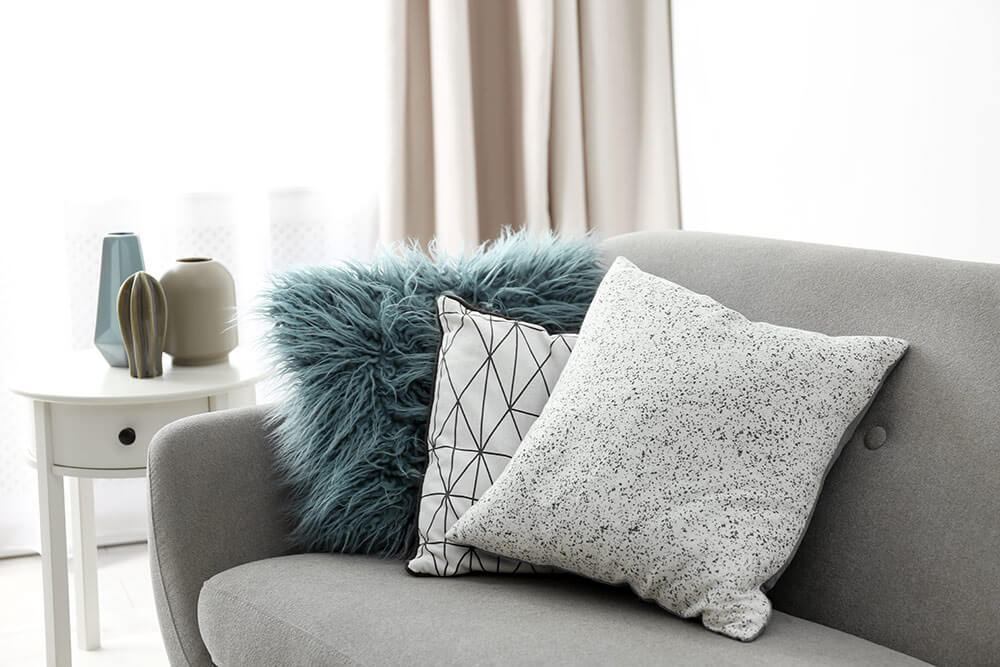 Fun, colorful decorative pillows on grey couch in downtown loft apartment