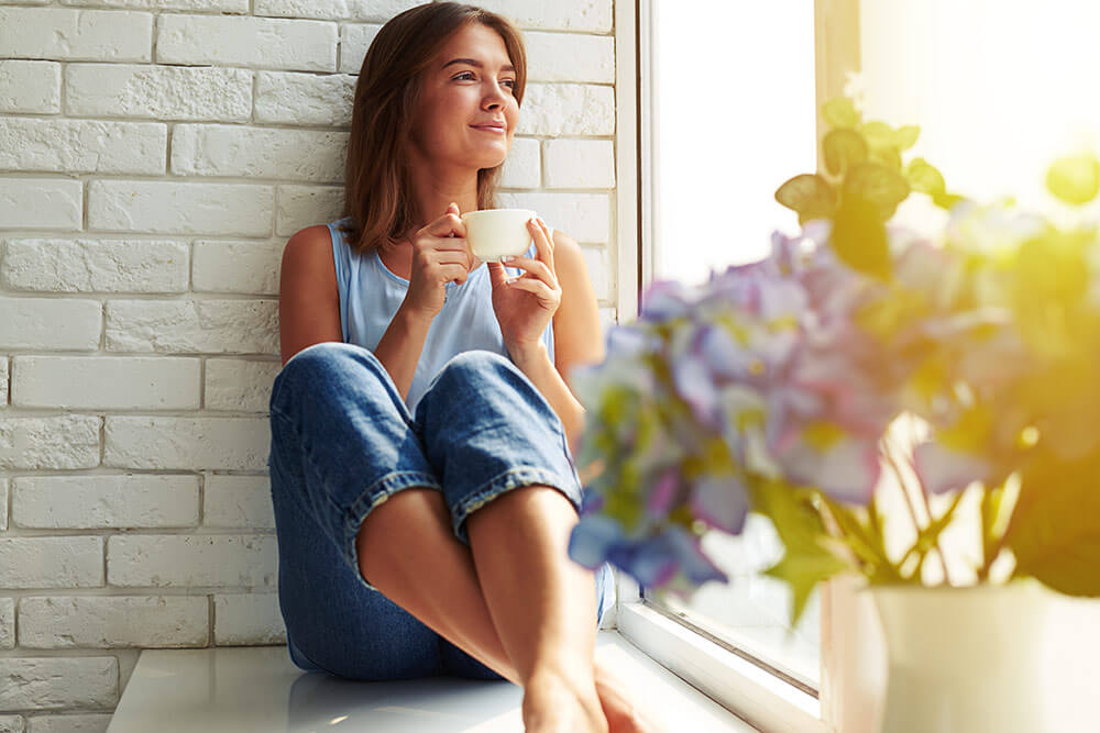 Woman relaxing near window with cup of coffee in hand and plants in foreground