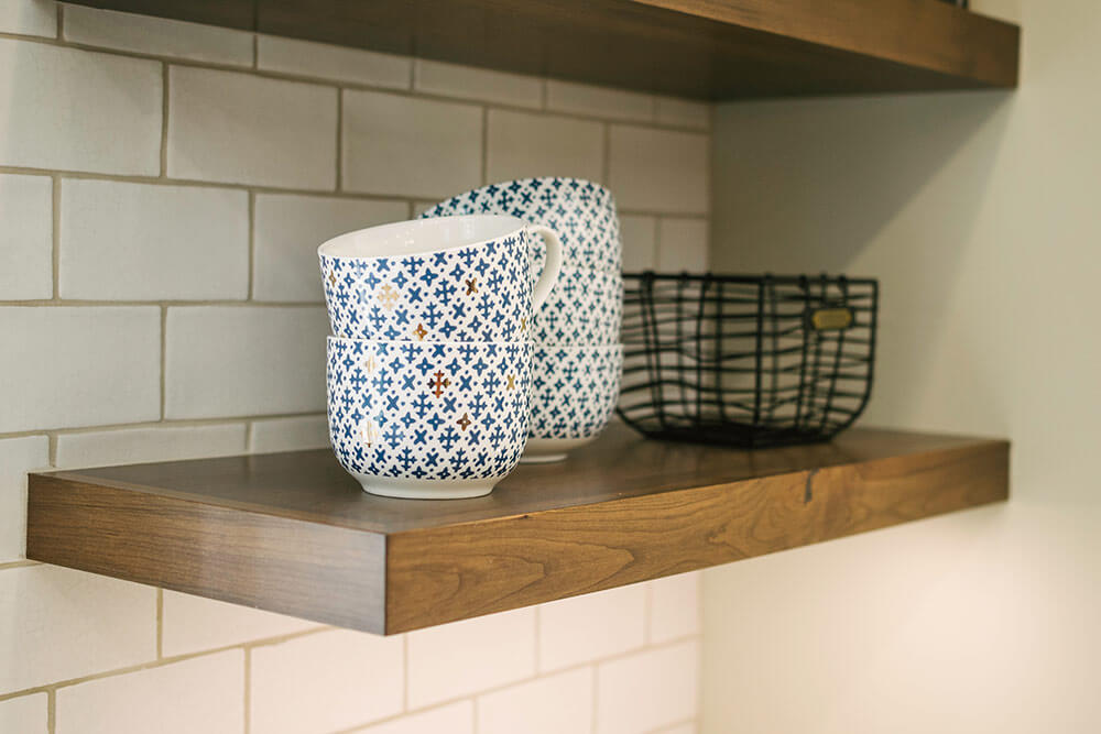 Floating wood shelf on wall with bowls in kitchen